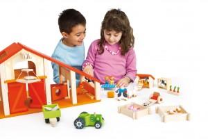 une maison de poupées en bois particulière qui représente une ferme avec sa grange, où pourront jouer les garçons comme les filles