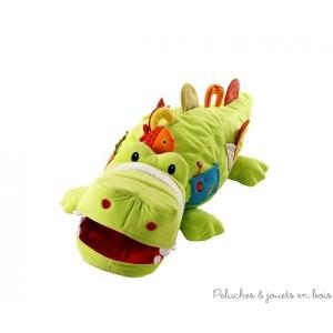 Théophile est un crocodile géant en forme de mini pouf, destiné à ranger les plus grands trésors et les petits objets. Favorise l'éveil des sens par différents sons, couleurs et matières. Avec des hochets dont un détachable, un miroir, des poignées une immense bouche range secret, une pochette et des écailles dorsales en papier bruissant. Dimensions  93 x 40 cm.