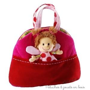 Un sac à main réversible avec deux poches, une poupée, un téléphone prtable avec sonerie et mirroir, un poudrier, un porte-monnaie et une clé en bois de la marque Lilliputiens. A partir de 1 an+