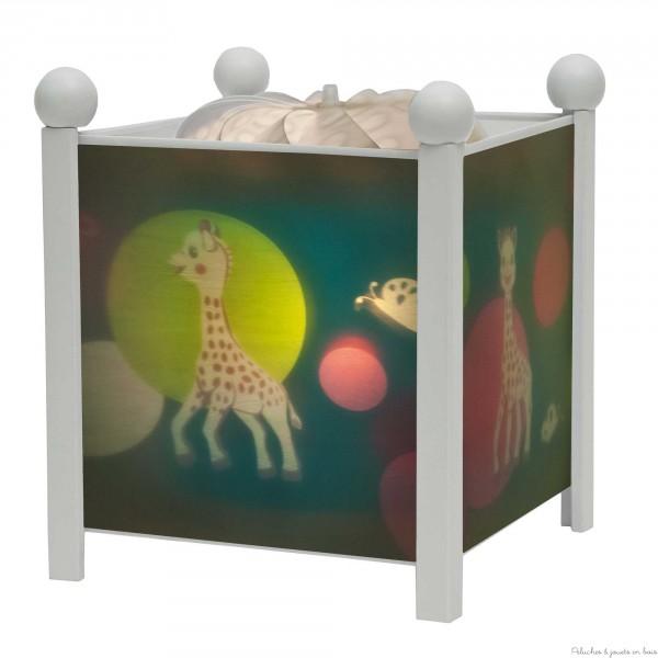 """Découvrez la lanterne magique ''Sophie la Girafe©"""" de Trousselier. Idéale pour endormir et rassurer bébé, cette lanterne animée montre à l'enfant des images qui défilent grâce à la chaleur de l'ampoule qui fait tourner une hélice. Sans danger avec son transformateur, ampoule transparente  12 V 20 W culot E 14 fournie.  Dim 16,50 cm x 19 cm. Matériaux : structure métallique, pieds en bois blanc et cylindre plastique résistant à la chaleur. Elle sera un superbe élément de décoration pour une atmosphère douce et apaisée dans la chambre de votre enfant. Livré dans sa boite cadeau Trousselier. Marque française Trousselier depuis 40 ans. Normes CE EN 60598-2-10"""