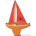 Mon grand voilier en bois avec une coque orange et des voiles rouges fabriqué en France signé Vilac. A partir de 3 ans+