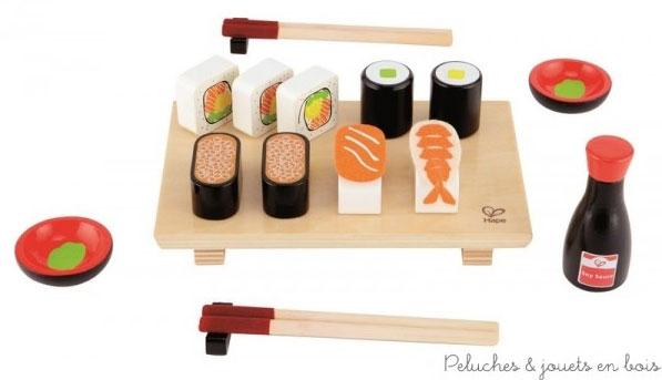 Un assortiment de sushi en bois fraichement préparés servi sur un plateau en bois avec 2 paires de baguettes, 2 coupelles à sauce et un flacon de sauce soja, de la marque Hape. A partir de 3 ans+