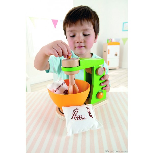 Un robot de cuisine mixer de la marque Hape avec un sachet de sucre et de farine. Prépare ton gâteau comme maman avec ce magnifique robot, il suffit de tourner le bouton du robot et les batteurs tournent. Rabats-les pour retirer ton bol. Bois massif peint. Normes CE