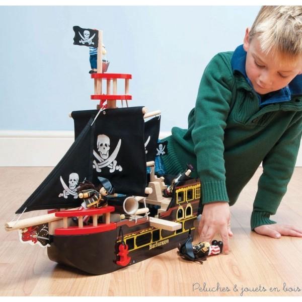 Un classique bateau de pirate en bois peint avec des voiles en tissus aux motifs de tête de mort et de sabres croisés de la marque Le Toy Van. A partir de 3 ans+
