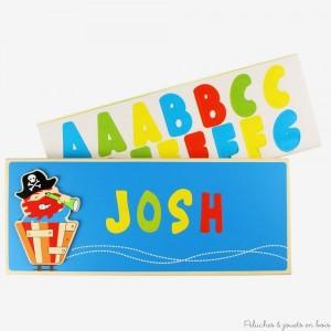 Une plaque de porte en bois bleu foncé sur le thème pirate de la marque Bigjigs, avec des lettres multicolores adhésives pour écrire le prénom. Pour la décoration de chambre d'enfant.