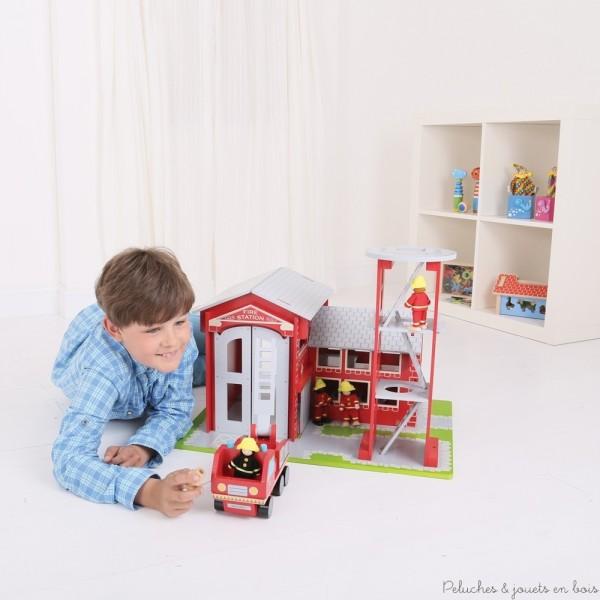 Un très bel ensemble en bois peint comprenant une caserne de pompiers, un camion de pompiers, une tour d'exercices et 4 pompiers articulés de la marque Bigjigs.  A partir de 3 ans+