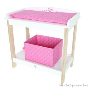 Une jolie table à langer en bois pour poupée,avec matelas à langer et coffre de rangement, un ensemble de couleur bois naturel, blanc et rose de la marque Hape. A partir de 3 ans+