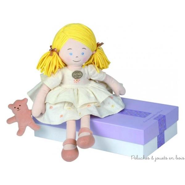 Soigneusement vêtue d'une robe aux motifs fleuris elle tient dans sa main un adorable petit ourson beige et séduira toutes les petites filles qui l'adopteront au premier regard. Livrée en boite cadeau mauve. Taille  43 cm. Lavable à 30°. Normes CE.