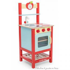 Dans la collection Honeybake de la marque Le Toy Van, une cuisinière petite pomme en bois peint ref TV311. Cette jolie cuisine comprend une double plaque de cuisson avec boutons cliquetis, un évier, un four avec grille en bois et étagère basse, un porte torchon et son torchon à pommes, une étagère haute et une horloge en forme de pomme aux aiguilles mobiles. A partir de 3 ans+