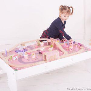 Rien ne manque dans ce très bel ensemble en bois, train et table magique de la marque Bigjigs Rail. Une pincée de poussière de fée a juste été ajoutée pour lui faire voir la vie en rose. A partir de 3 ans+