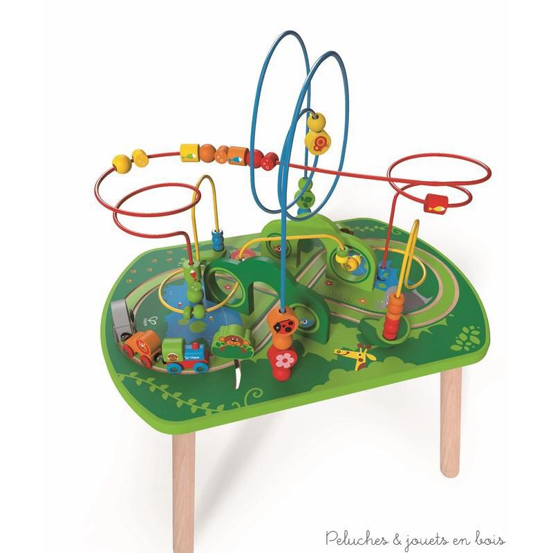 Dans la gamme Trains en Bois de la collection Hape, Une table d'activités avec des labyrinthes à perles multicolores et un circuit de train avec petit train des animaux qui se promène à travers la jungle. A partir de 18 mois+