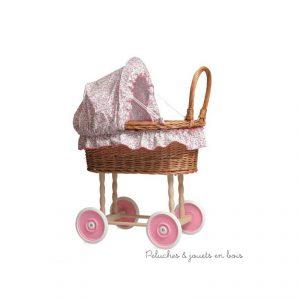 Un landau en osier avec capote et garniture à petites fleurs rose de la marque Egmont Toys. A partir de 3 ans+