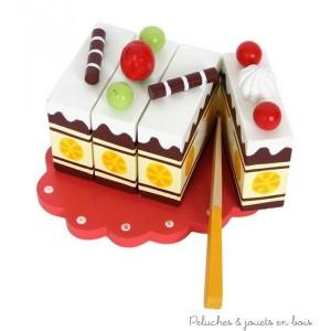 Un gâteau en bois verni coloré à découper, avec un système d'attaches à scratch, à l'aspect alléchant, avec son plateau de service et un couteau en bois. A partir de 3 ans+