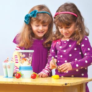 ensemble à fabriquer des smoothies complet comprenant un robot avec un bol amovible, 6 fruit à découper avec des velcros et un couteau en bois, ainsi que 2 coupes en bois avec une paille et une garniture amovible pour servir tes smoothies de fruit. A partir de 3 ans+