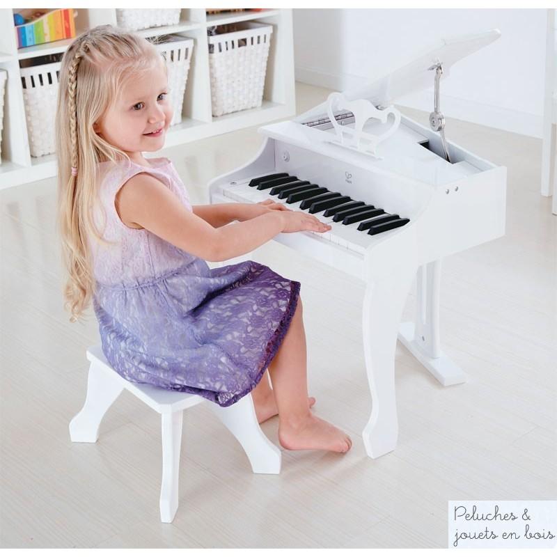 Un ensemble piano à queue électronique blanc et son tabouret en bois signé Hape. Les pianistes en herbe pourront facilement pianoter sur les 30 touches de ce vrai piano électronique. Fait pour les petites mains et la grande musique il permettra de composer ses propres petites symphonies. A partir de 3 ans+