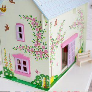 Une grande et jolie Maison de poupées rose, blanche et mauve en bois de la marque Bigjigs entièrement meublée et habitée par une petite famille, un chien et un chat . A partir de 3 ans+