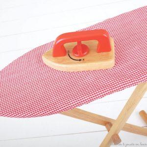 Une planche à repasser et un fer à repasser en bois avec un bouton on/off. Un Jouet d'imitation en bois peint, solide et pliable, parfait complément de l'étendoir à linge et de la machine à laver ! Dimensions : 65 x 63 x 20 cm. Normes CE EN71.